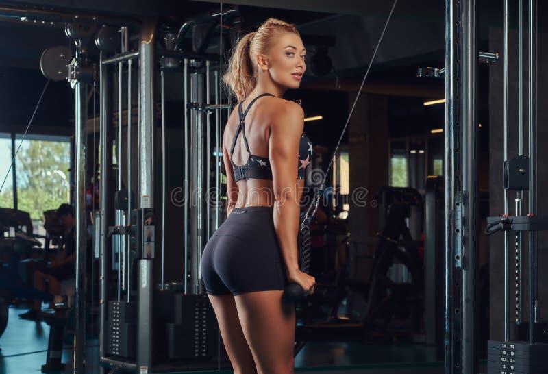 Sportowa blondynki kobieta w sportswear robi ćwiczeniu na triceps na skrzyżowanie maszynie w gym zdjęcie royalty free