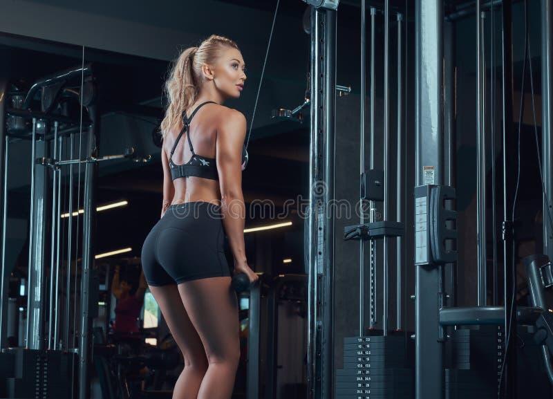 Sportowa blondynki kobieta w sportswear robi ćwiczeniu na triceps na skrzyżowanie maszynie w gym obrazy stock