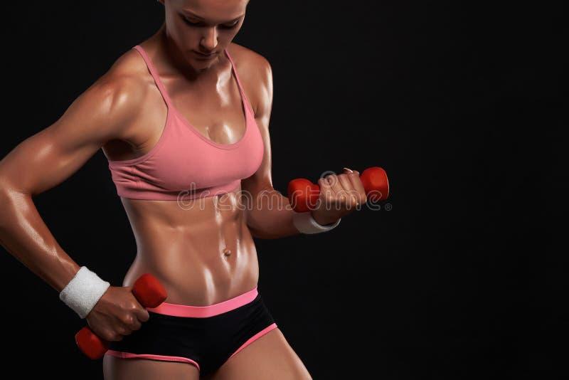 Sportowa bodybuilder kobieta z dumbbells piękna blondynki dziewczyna z mięśniami zdjęcia royalty free