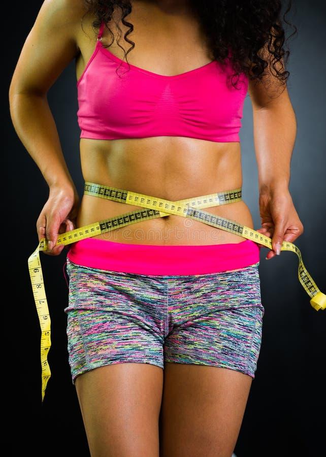 Sportowa brunetki kobieta jest ubranym menchia wierzchołek i dopasowywa skróty, zbliżenie żołądek podczas gdy pomiarowy podbrzusz obrazy stock