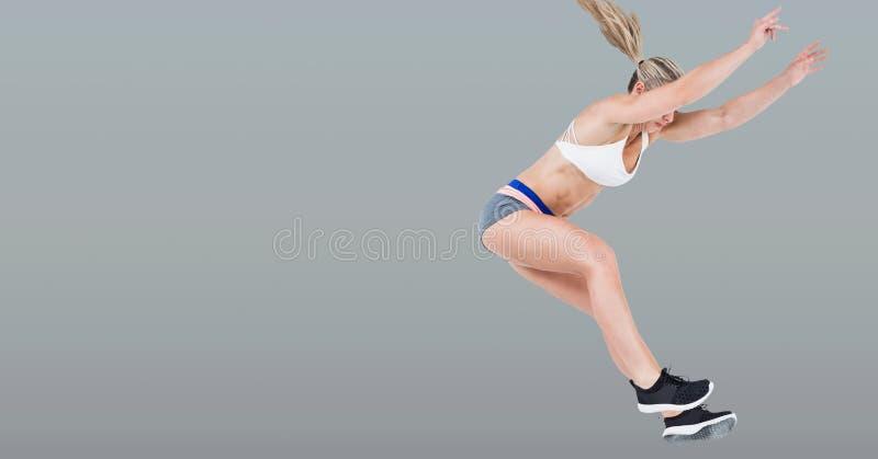 Sportowa dysponowana skokowa kobieta z pustego miejsca popielatym tłem obrazy royalty free