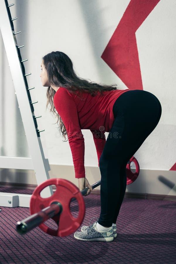 Sportowa dziewczyna angażująca w sprawności fizycznej weightlifting kobieta podnosi barbell fotografia stock