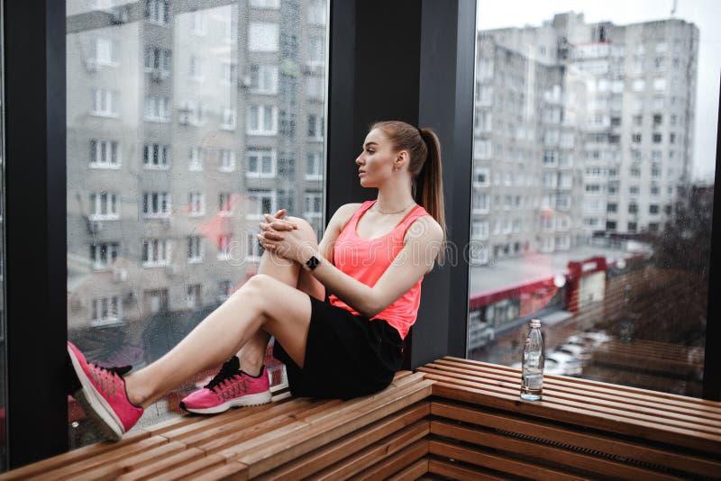 Sportowa dziewczyna ubierający sport zwiera i koszulka siedzi na drewnianym windowsill w nowożytnym gym obraz royalty free