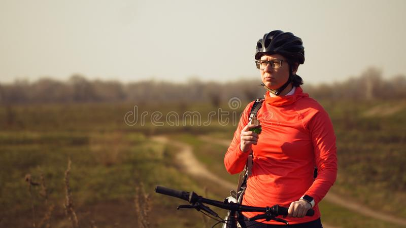 Sportowa Kaukaska kobieta je proteina baru przeja?d?k? na rowerze g?rskim na naturze M?oda sporty kobiety atleta odpoczywa w he?m obrazy stock