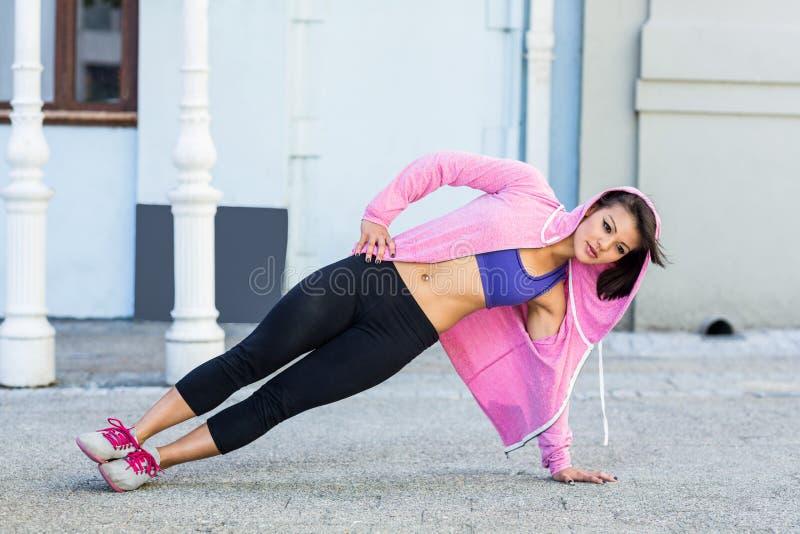 Sportowa kobieta ćwiczy boczną deskę zdjęcie stock