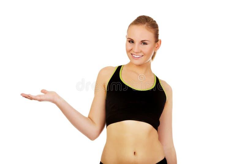 Sportowa kobieta przedstawia coś na otwartej palmie w sport bieliźnie obraz royalty free