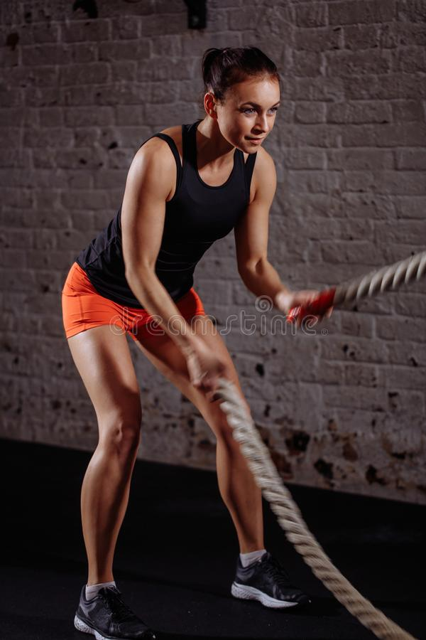 Sportowa kobieta robi niektóre przecinającemu napadowi ćwiczy z batalistyczny linowy salowym fotografia stock