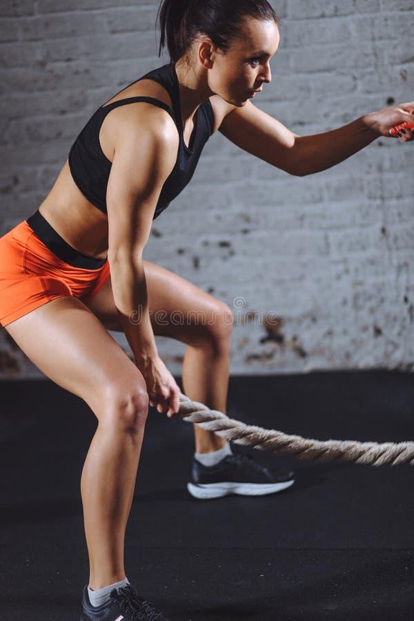 Sportowa kobieta robi niektóre przecinającemu napadowi ćwiczy z batalistyczny linowy salowym fotografia royalty free