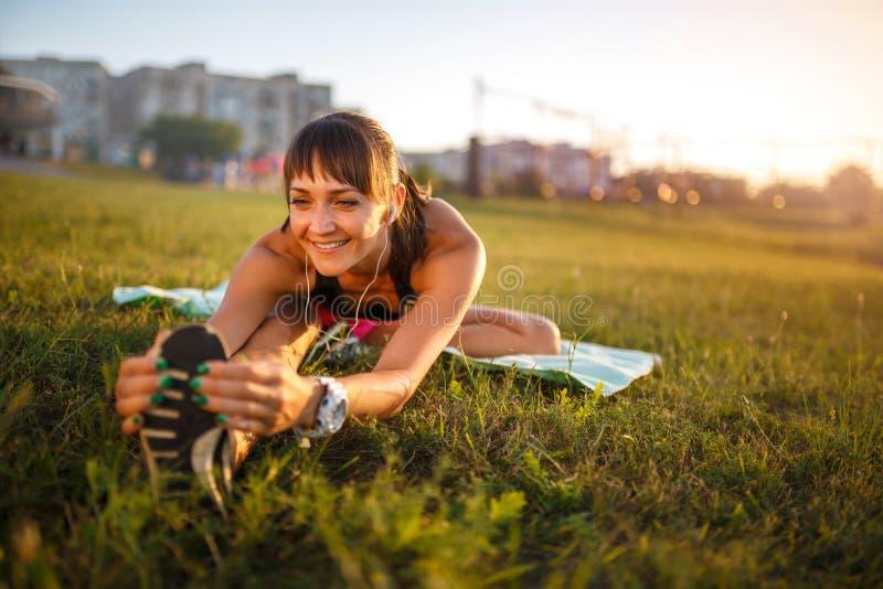 Sportowa kobieta rozciąga jej ścięgno, nogi ćwiczenia stażowa sprawność fizyczna przed treningiem outside z hełmofonami słucha mu obraz stock