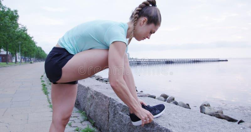 Sportowa kobieta wiąże jej koronki przed biegać obraz stock