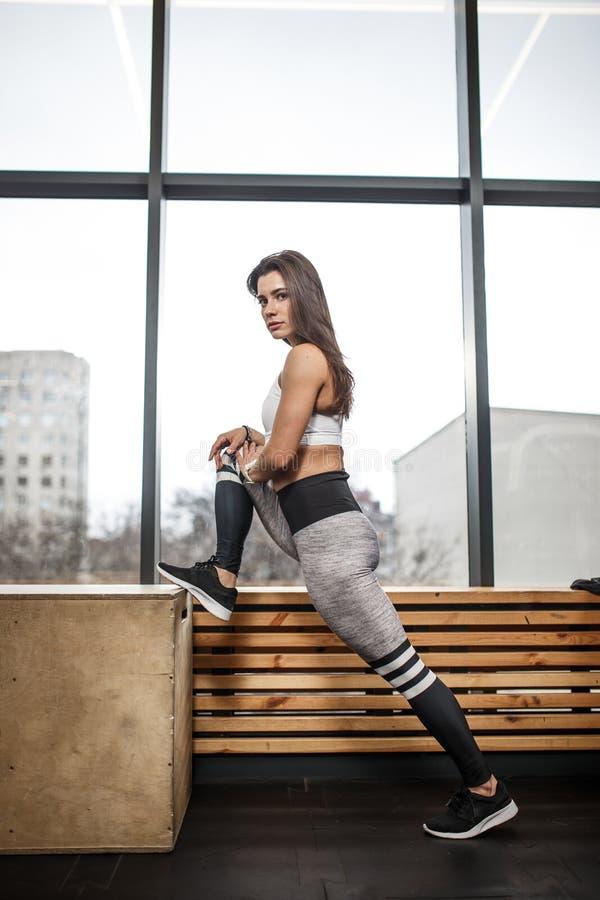 Sportowa młoda brunet dziewczyna ubierająca w sportswear robi rozciąganiu obok drewnianego windowsill i panoramicznego zdjęcie stock