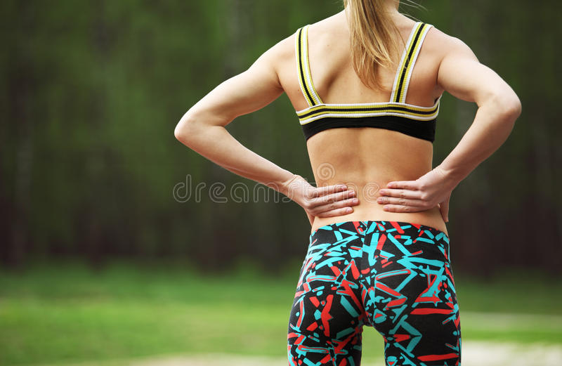 Sportowa młoda kobieta naciera mięśnie jej niski z powrotem obraz stock