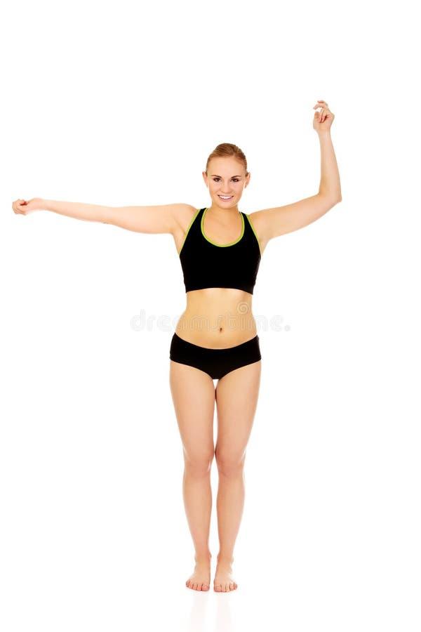 Sportowa młoda kobieta robi ręk ćwiczeniom zdjęcia stock