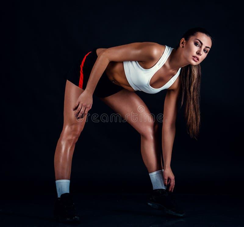 Sportowa młoda kobieta robi sprawność fizyczna treningowi przeciw czarnemu tłu Sporty kobieta w sportswear z perfect sprawności f zdjęcia stock