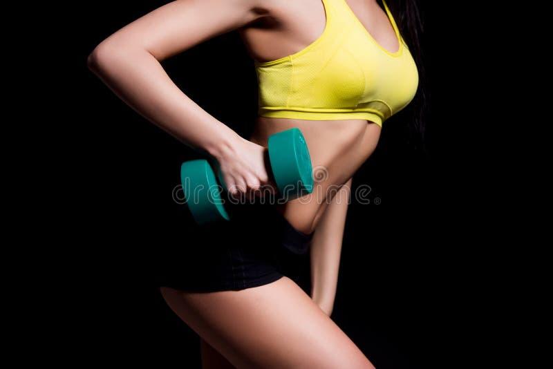 Sportowa młoda kobieta robi sprawność fizyczna treningowi z dumbbells na czarnym pracownianym tle fotografia stock