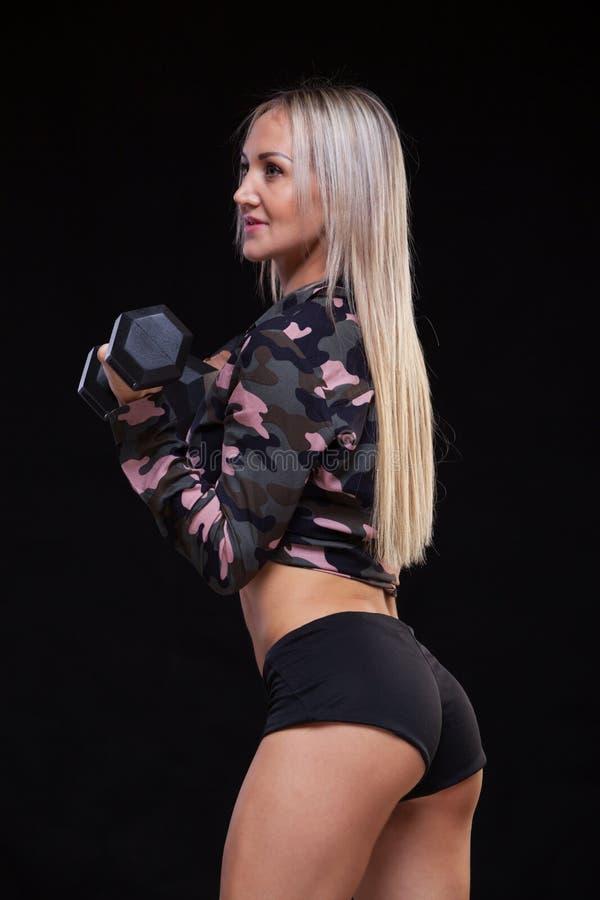 Sportowa młoda kobieta robi sprawność fizyczna treningowi z dumbbells na czarnym pracownianym tle w ubraniach militarni kolory fotografia royalty free