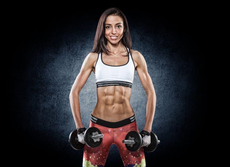 Sportowa młoda kobieta robi treningowi z ciężarami na ciemnym backgrou obraz stock