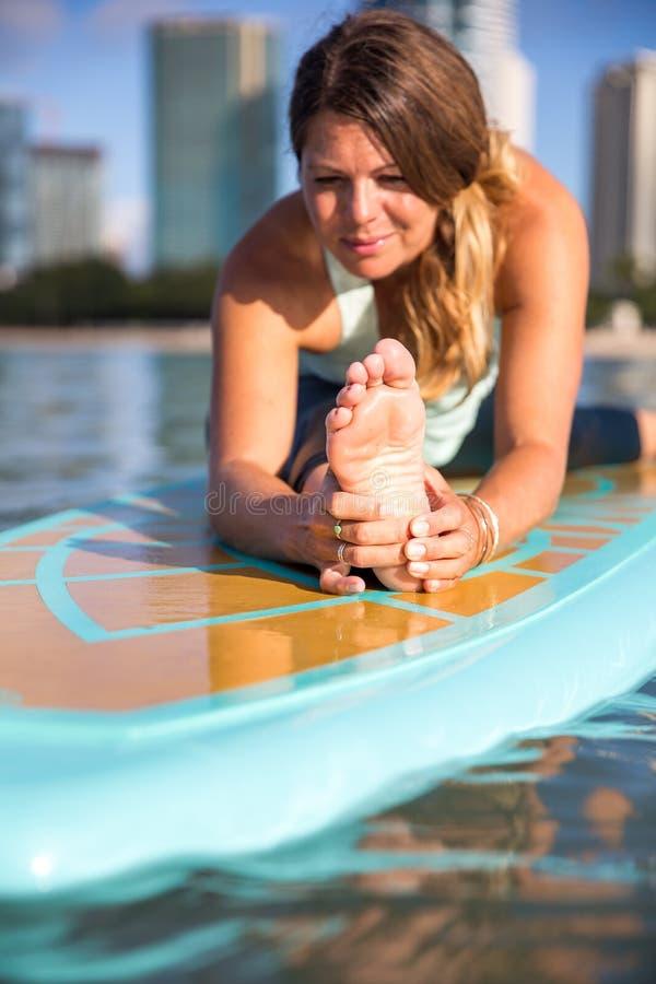 Sportowa młoda kobieta w SUP joga praktyki przodu rozciągliwości w ałunach M zdjęcia stock
