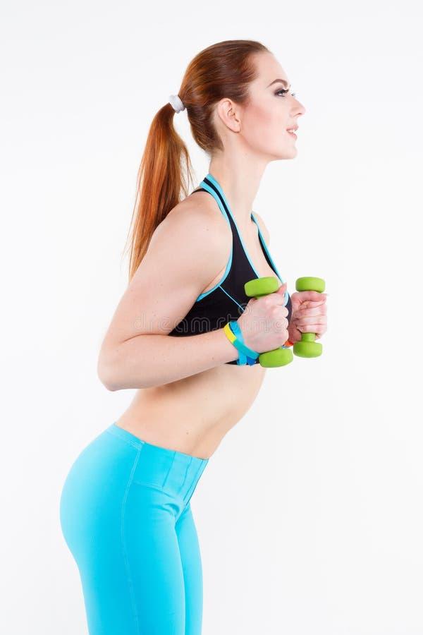 Sportowa miedzianowłosa kobieta w jaskrawym sportswear robi ćwiczeniu z małymi zielonymi dumbbells zdjęcie royalty free