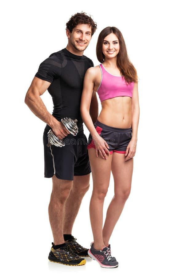 Sportowa para - mężczyzna i kobieta z dumbbells na bielu zdjęcia stock