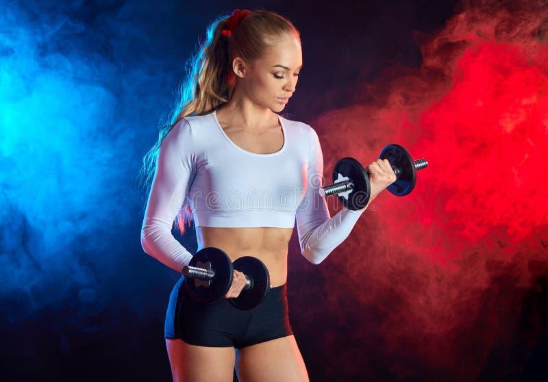 Sportowa pi?kna m?oda kobieta robi sprawno?? fizyczna treningowi z dumbbells obraz royalty free