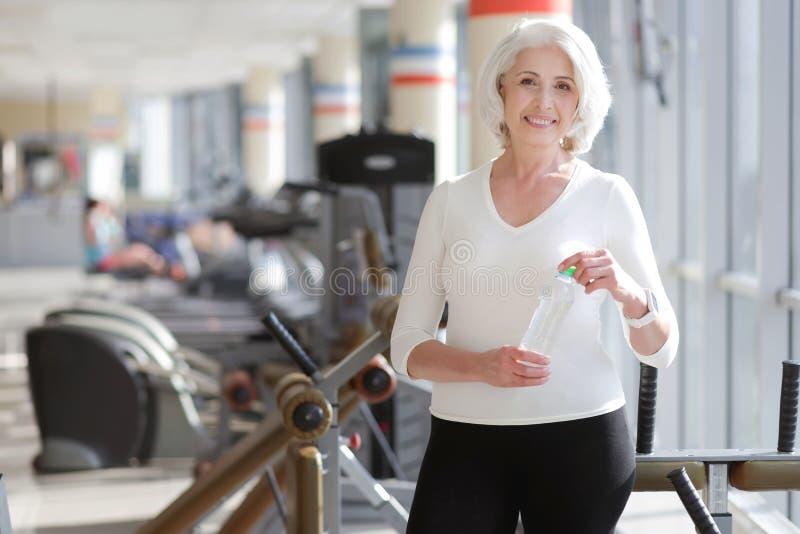 Sportowa powabna starsza kobieta ma odpoczynek podczas gym treningu fotografia stock