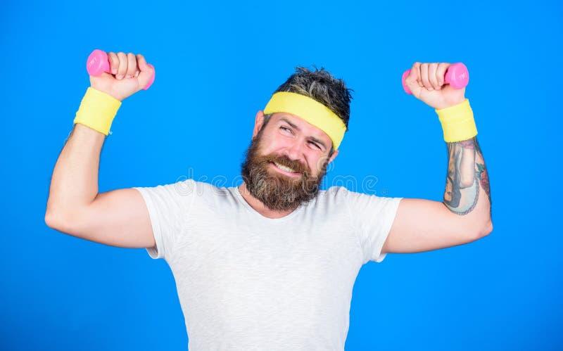 Sportowa szkolenie z dumbbells błękita tłem Ulepsza twój mięśnie Używa ciężary lub dumbbells Mężczyzna brodata atleta obraz royalty free