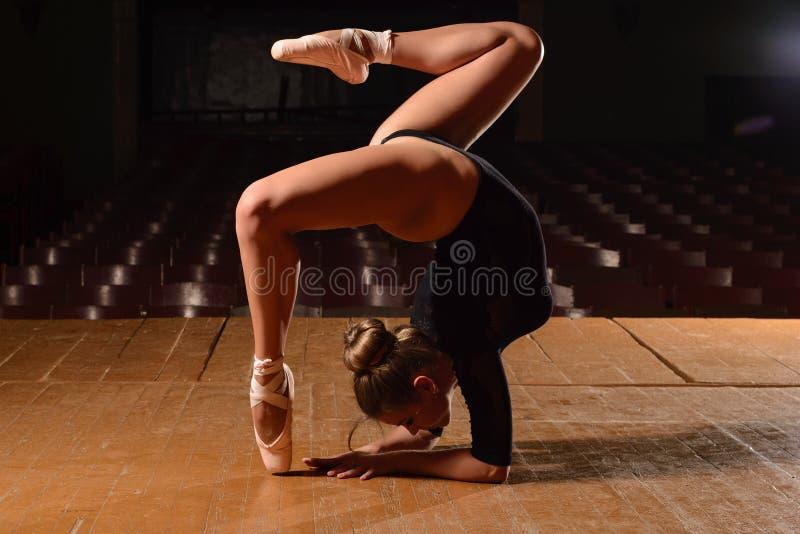 Sportowe gimnastyki w pointes zginali teatr scena zdjęcia royalty free