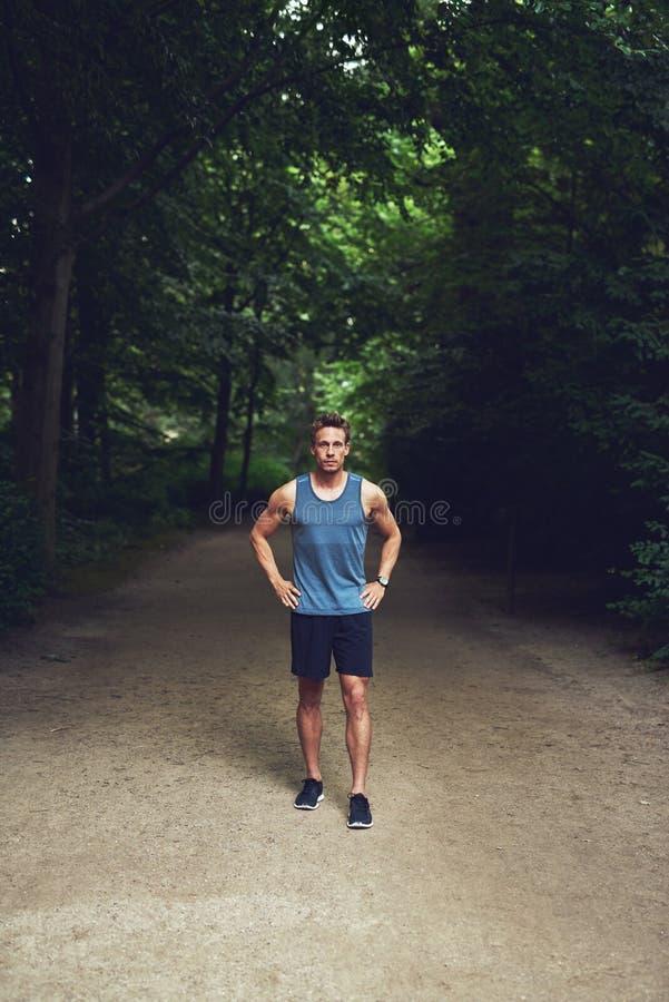 Sportowego młodego człowieka trwanie czekanie w parku zdjęcie stock