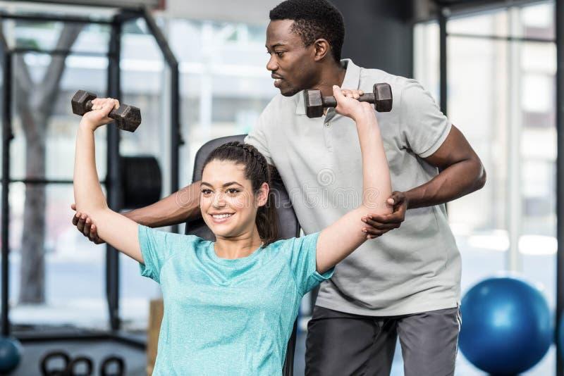 Sportowi kobieta udźwigu ciężary pomagać trenerem zdjęcie royalty free