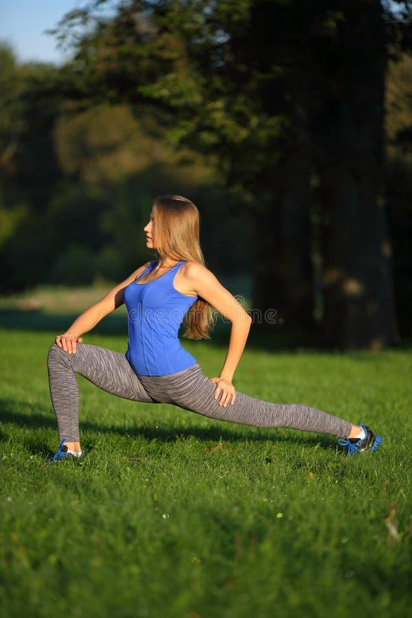 Sportowi piękni dziewczyn thrustes w parkowy patrzeć daleko od obraz stock