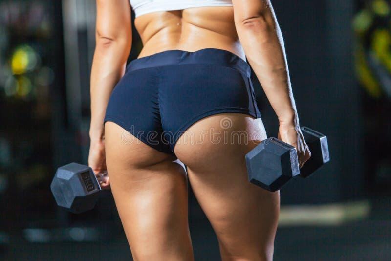 Sportowi pośladki jest ubranym sporty skróty z dumbbells w gym plecy widoku dysponowana dziewczyna obrazy royalty free