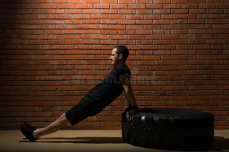 Sportowiec robi ćwiczeniu z jego swój ciężarem opiera na oponie na tle czerwony ściana z cegieł obraz royalty free