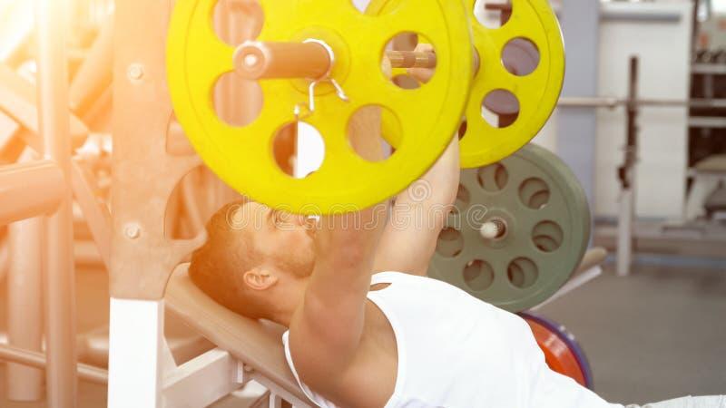 Sportowiec robi barbell ławki odciskaniu podczas gdy ćwiczący przy sprawność fizyczna klubem Mięśniowy mężczyzna Ćwiczy W Gym fotografia royalty free