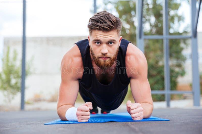 Sportowiec robi deski ćwiczeniu na błękitnej sprawności fizycznej macie podczas treningu zdjęcia royalty free