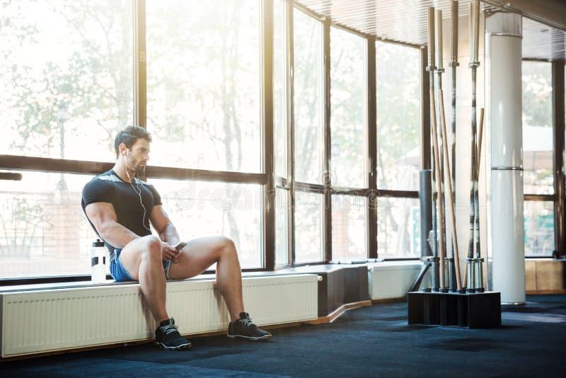 Sportowiec słucha muzyczny obsiadanie na windowcill obrazy royalty free