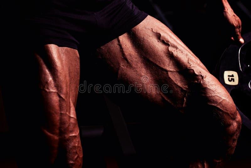 Sportowiec w gym Facet robi ćwiczeniom Zbliżenie portret nogi z żyłami Samiec model z garbnikującą skórą człowiek sexy obrazy stock