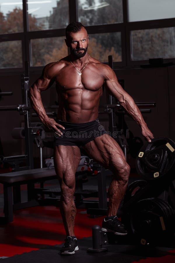Sportowiec w gym Mięśniowy sportowy mężczyzna stoi blisko barbell Brutalna samiec z garbnikującą skóry i mięśnia półpostacią zbli obrazy stock