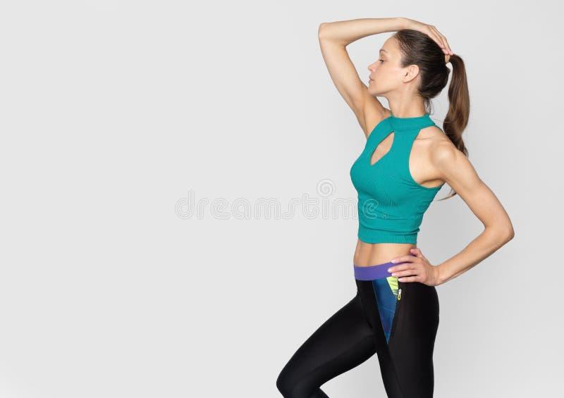 sportowiec wykonuje ćwiczenia w odosobnieniu na szaro zdjęcie stock