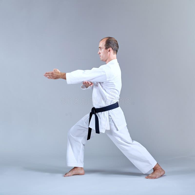 Sportowiec z czarnym paskiem karategi i trenuje formalnych karatych ćwiczenia fotografia royalty free
