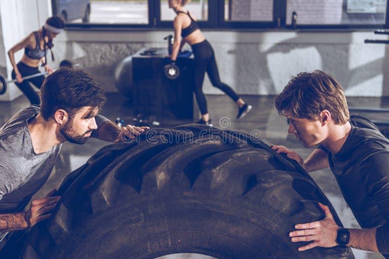 Sportowowie ćwiczy z dużą oponą przy gym treningiem zdjęcia royalty free