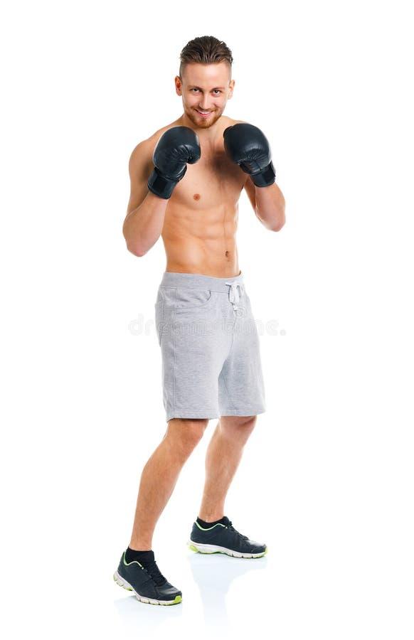 Sportowy atrakcyjny mężczyzna jest ubranym bokserskie rękawiczki na bielu obraz royalty free