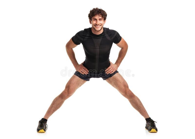 Sportowy atrakcyjny mężczyzna robi sprawności fizycznej exersise na bielu zdjęcie royalty free