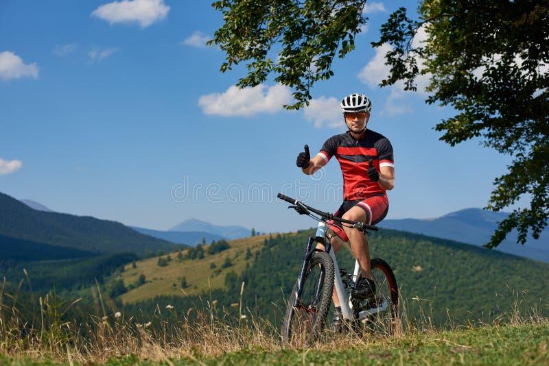 Sportowy cyklista w sportswear i hełma kolarstwa rowerze górskim, seans aprobaty, jedzie zdjęcia stock