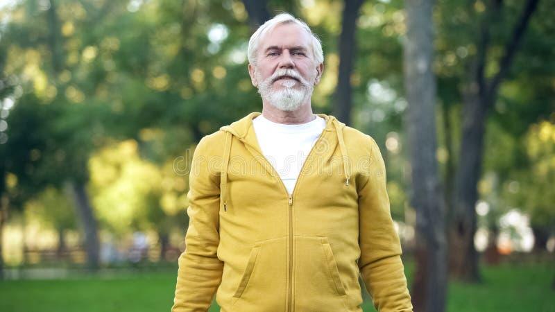 Sportowy dojrzały mężczyzna robi rankowi ćwiczy w parku, zdrowy styl życia, starzeje się obraz royalty free