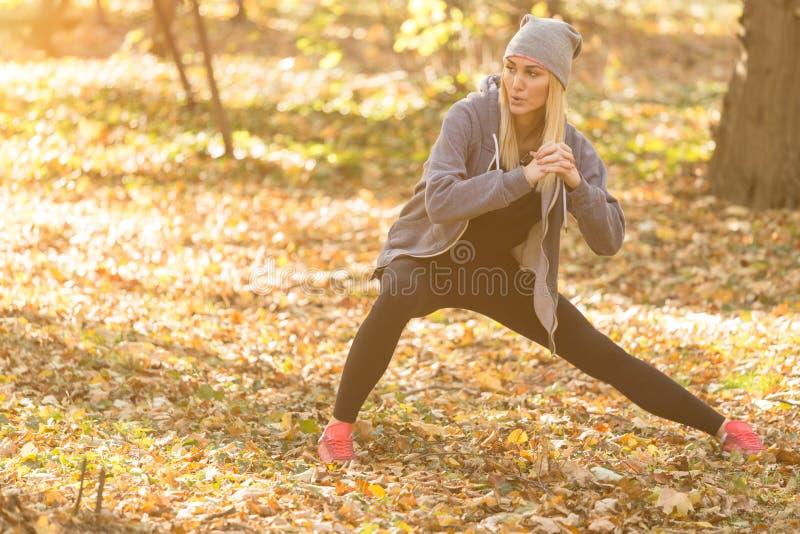 Sportowy dziewczyna bieg w parku i robić ćwiczymy zdjęcia royalty free