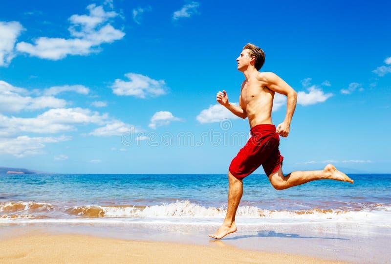 Sportowy mężczyzna bieg na plaży zdjęcia royalty free