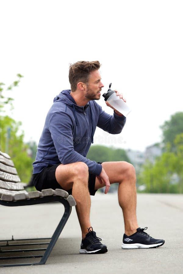 Sportowy mężczyzna obsiadanie na ławki wodzie pitnej fotografia stock