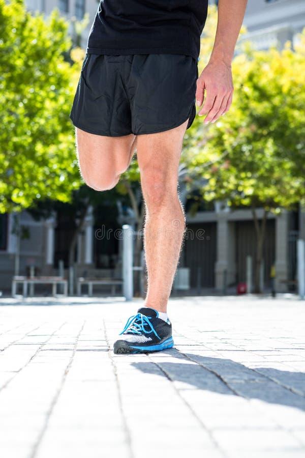 Sportowy mężczyzna robi nogi rozciąganiu zdjęcie stock