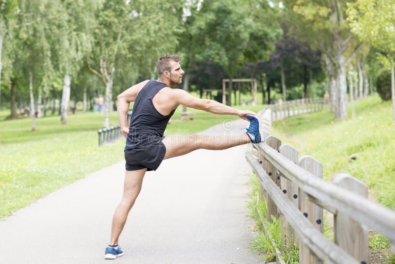 Sportowy mężczyzna robi rozciągliwość przed ćwiczyć, plenerowy zdjęcie royalty free